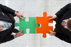 Homens de negócios que montam o enigma de serra de vaivém que representa trabalhos de equipa Foto de Stock
