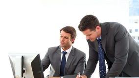 Homens de negócios que olham a fala do tela de computador filme