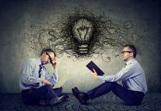 Homens de negócios que sentam-se em um assoalho no escritório usando o portátil que lê um livro com pensamentos da ampola e da id Fotografia de Stock Royalty Free