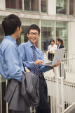 Homens de negócios que sorriem e que trabalham junto fora com portátil Imagem de Stock