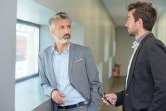 Homens de negócios que têm a conversação no corredor fotografia de stock royalty free