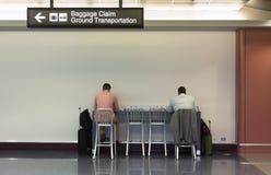 Homens de negócios que trabalham na estação de carregamento do aeroporto Fotos de Stock Royalty Free