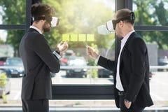 Homens de negócios que vestem auriculares da realidade virtual ao trabalhar no escritório Fotos de Stock Royalty Free