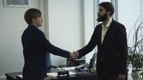 Homens de negócios sérios nos revestimentos do terno que agitam as mãos durante a reunião do escritório Conceito da parceria filme