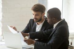 Homens de negócios sérios que discutem o documento da empresa no escritório Fotos de Stock Royalty Free