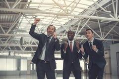 Homens de negócios satisfeitos que florescem os braços internos imagem de stock royalty free