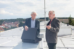 Homens de negócios superiores que discutem o negócio de negócio no telhado de um bui Foto de Stock Royalty Free