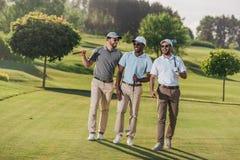 Homens de sorriso nos tampões e nos óculos de sol que guardam clubes de golfe e que andam no gramado imagem de stock