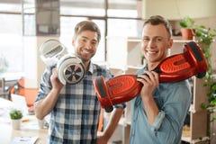 Homens de sorriso positivos que guardam 'trotinette's do giroscópio fotografia de stock royalty free