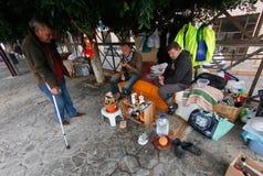 Homens desabrigados que tomam seu café da manhã em seu banco Foto de Stock Royalty Free
