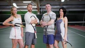 Homens desportivos e mulheres que levantam com as raquetes no campo de tênis filme