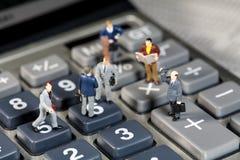 Homens diminutos que agitam as mãos em uma calculadora Imagem de Stock