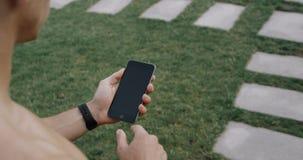 Homens do corredor que guardam o smartphone usando o écran sensível para escolher o exercício no app antes de correr na trilha vídeos de arquivo