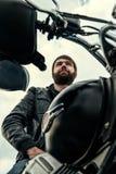 Homens do motociclista com uma barba que senta-se em sua motocicleta fotos de stock royalty free