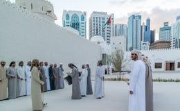 Homens do Oriente Médio de Emirati que executam o Yowla, uma dança tradicional na cultura de Emiratos Árabes Unidos fotografia de stock