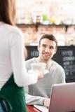 Homem novo que está sendo serido no café Fotos de Stock Royalty Free