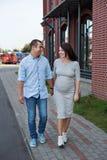 Homens dos pares da família e uma mulher gravida nova que anda guardando as mãos e rindo ao longo das janelas da cidade Foto de Stock