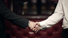 Homens dos sócios comerciais que fazem um aperto de mão Movimento lento