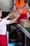 Homens durante o trabalho no armazém de distribuição Imagem de Stock