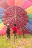 Homens e balão de ar quente na terra Imagens de Stock Royalty Free