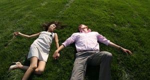 Homens e mulher que encontram-se na grama fotografia de stock royalty free