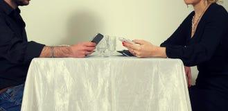Homens e mulher que jogam com os telefones Foto de Stock Royalty Free