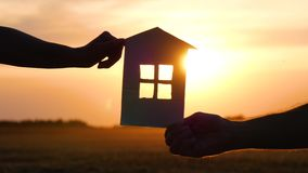 Homens e mulheres das mãos que guardam uma casa de papel A silhueta da casa Conceito feliz da família, da construção e da hipotec filme
