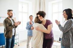 Homens e mulheres durante a terapia do grupo, mostrando um sinal do relevo imagem de stock