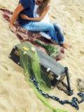 Homens e mulheres nas calças de brim que encontram-se em uma cobertura da manta na areia na praia Imagens de Stock