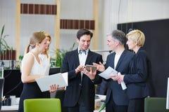 Homens e mulheres no escritório com PC da tabuleta imagem de stock royalty free