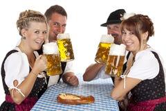 Homens e mulheres que bebem a cerveja de Oktoberfest Fotografia de Stock