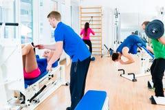 Homens e mulheres que fazem o exercício no equipamento diverso no gym foto de stock royalty free
