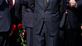 Homens em ternos pretos restritos com flores vermelhas Gest?o da empresa A delegação oficial fotos de stock