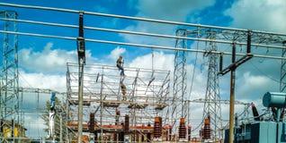 Homens em trabalhadores preliminares da subestação da distribuição da eletricidade do trabalho fotos de stock royalty free