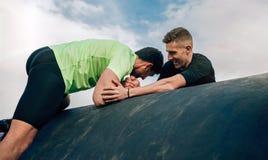 Homens em um curso de obstáculo que escala um cilindro foto de stock royalty free