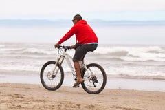 Homens em um hoodie vermelho em uma bicicleta fotos de stock royalty free