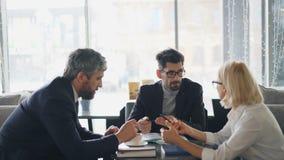 Homens farpados que discutem detalhes do contrato com a mulher de negócios superior no café vídeos de arquivo