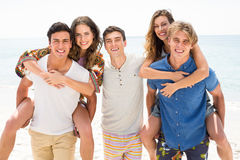 Homens felizes que rebocam mulheres na praia Fotografia de Stock