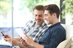 Homens felizes que verificam o índice em linha na tabuleta e no telefone imagem de stock royalty free