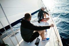 Homens fortes consideráveis que navegam com seu barco Imagem de Stock