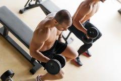 Homens fortes que levantam os pesos que sentam-se no banco Fotografia de Stock Royalty Free