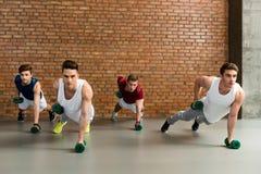 Homens fortes que treinam com pesos Fotos de Stock Royalty Free