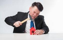 Homens irritados que guardam o martelo sobre a casa de papel vermelha Imagens de Stock Royalty Free