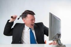 Homens irritados que guardam o martelo sobre o monitor do PC Imagem de Stock