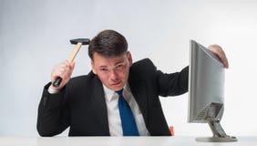 Homens irritados que guardam o martelo sobre o monitor do PC Fotos de Stock Royalty Free