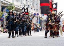 Homens japoneses na armadura do samurai que guarda armas