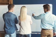 Homens jovens e senhora que participam no treinamento no escritório imagens de stock royalty free