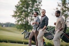 Homens multi-étnicos que guardam sacos com clubes de golfe e que andam no campo de golfe fotos de stock royalty free