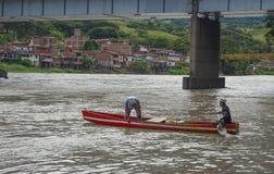 Homens nas canoas que passam o rio Antioquia imagem de stock