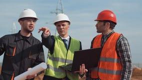 Homens no terreno de construção que discutem o modelo Imagem de Stock